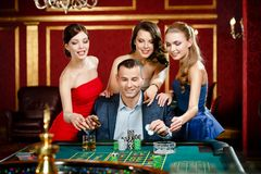Man surrounded by women plays roulette Royalty Free Stock Photo