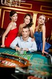 Man surrounded by young girls gambles roulette Stock Photography