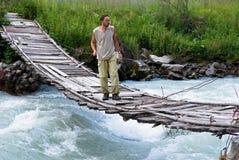 Man on suspension bridge Stock Images