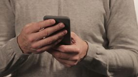 Man in sweater chatting on the phone on white background. People and communoication stock footage