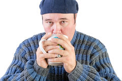 Man in sweater drinking hot beverage looking up Stock Photos