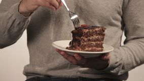Man in sweater eating a big piece of chocolate cake stock footage