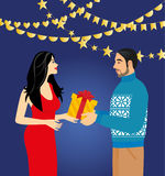 A man in a sweater gives a gift a beautiful woman in a red dress Stock Image