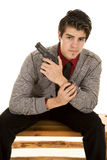 Man in sweater holding gun sitting looking Stock Images