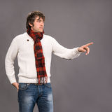 Man in sweater pointing his finger on a gray background Stock Image