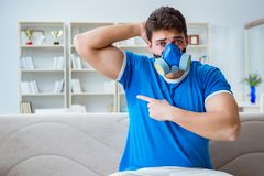 The man sweating excessively smelling bad at home. Man sweating excessively smelling bad at home royalty free stock image