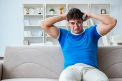 The man sweating excessively smelling bad at home. Man sweating excessively smelling bad at home stock photography