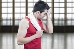Man sweating. Sportsman sweating with a towel in  a sports hall Royalty Free Stock Photo
