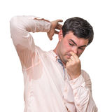 Man with sweating under armpit pinches nose with fingers. Isolated on white Royalty Free Stock Images