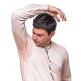 Man with sweating under armpit in pink shirt isolated on white. Young man with sweating under armpit in pink shirt isolated on white Royalty Free Stock Photography