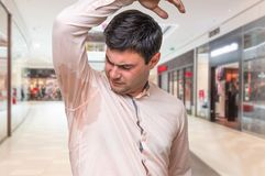 Man with sweating under armpit in shopping center. Young man with sweating under armpit in shopping center Royalty Free Stock Photo