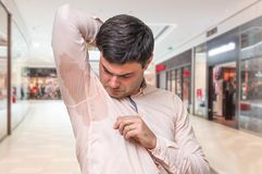 Man with sweating under armpit in shopping center. Young man with sweating under armpit in shopping center Royalty Free Stock Photos