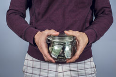 Man in a sweatshirt holds moneybox with money Stock Images