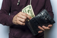 Man in a sweatshirt holds wallet with money Royalty Free Stock Images