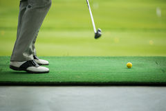 Man sweeping ball on golf course Royalty Free Stock Photo