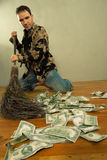 Man sweeping dollar banknotes. On the wooden floor Royalty Free Stock Photography