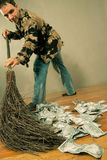 Man sweeping dollar banknotes. On the wooden floor Royalty Free Stock Photos