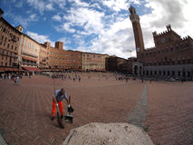 Man sweeping floor in square in Sienna Stock Photo