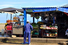 A man is sweeping in front of his food street vendor on the Con Dao island of Vietnam Royalty Free Stock Images