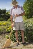 Man sweeping garden path Stock Photo
