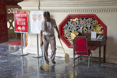 Man sweeping highly polished floor with brushes Royalty Free Stock Images