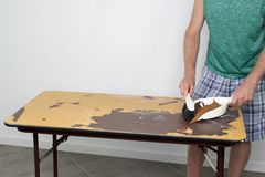 Man Sweeps Debris Off a Table Top He's Resurfacing. Male cleans off table he is preparing to resurface Male sweeping off a table with a dustpan and broom stock photo