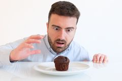 Greedy man tempted by sweet chocolate cake royalty free stock photos