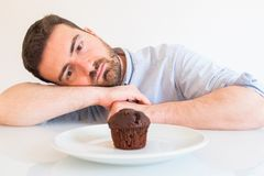 Greedy man tempted by sweet chocolate cake stock photography