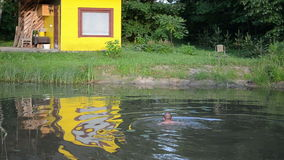 Man swim in dirty little garden pond water nea bath house stock video