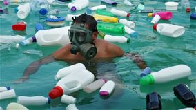 Man swim in plastic polluted water using protecting mask. Man swim in polluted water using protecting mask - loooking at the plastic trash floating stock video footage