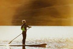 Man swim sup paddle board sunset. Man swims on sup paddle board at sunset time. Paddleboarding concep stock photography