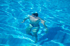 Man swim under blue water Stock Images