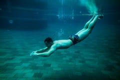 Man swim underwater pool. On vacation leisure time stock photos