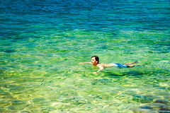 Man Swiming in Crystal Clear Sea stock image