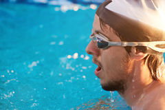 Man swimmer head. On blurred blue water pool background close-up Royalty Free Stock Images