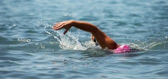 Man swimmer swimming crawl in blue sea. Training for triathlon Stock Photos