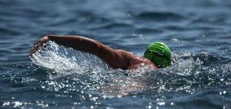 Man swimmer swimming crawl in blue sea. Training for triathlon Stock Image