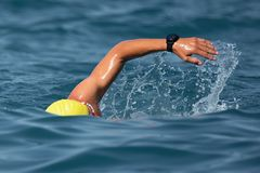 Man swimmer swimming crawl in blue sea. Unknown swimmer at sea, swimming crawl in blue sea,training for triathlon royalty free stock photography