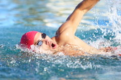 Man swimmer swimming crawl in blue water. Portrait of an athletic young male triathlete swimming crawl wearing a pink cap and swimming goggles while Stock Photography