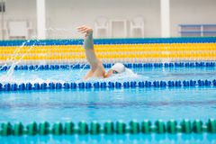 Man swimmer swimming crawl in blue water. Portrait of an athletic young male triathlete swimming crawl wearing a pink cap and swimming goggles while Royalty Free Stock Photos