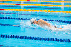 Man swimmer swimming crawl in blue water. Portrait of an athletic young male triathlete swimming crawl wearing a pink cap and swimming goggles while Royalty Free Stock Images