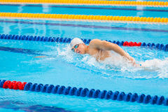 Man swimmer swimming crawl in blue water. Portrait of an athletic young male triathlete swimming crawl wearing a pink cap and swimming goggles while Royalty Free Stock Photography