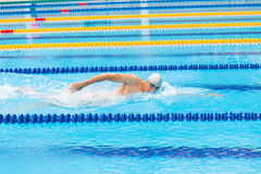 Man swimmer swimming crawl in blue water. Portrait of an athletic young male triathlete swimming crawl wearing a pink cap and swimming goggles while Royalty Free Stock Photo
