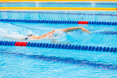 Man swimmer swimming crawl in blue water. Royalty Free Stock Images