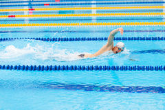 Man swimmer swimming crawl in blue water. Portrait of an athletic young male triathlete swimming crawl wearing a pink cap and swimming goggles while Stock Images