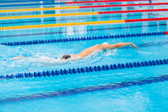 Man swimmer swimming crawl in blue water. Portrait of an athletic young male triathlete swimming crawl wearing a pink cap and swimming goggles while Royalty Free Stock Image