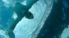 Man swimmer take an action camera from pool bottom. Underwater view stock footage