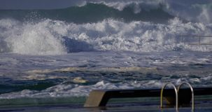 Man swimming with big waves hitting ocean baths. Man swimming with big ocean waves hitting ocean baths with white water stock video