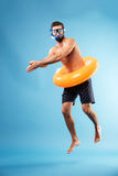 Man with swimming circle diving. Man wearing swimming glasses with swimming circle diving isolated over blue Stock Photos