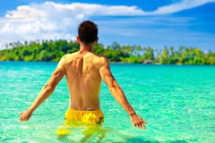 Man swimming in clear sea ocean water. On background amazing nature with wild tropical island and blue summer sky on horizon. Summer vacation in tropical Stock Image